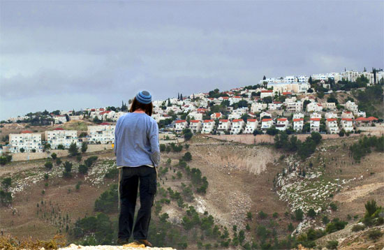 A Jewish settler looks at the West bank settlement of Maaleh Adumim, from the E-1 area on the eastern outskirts of Jerusalem, Wednesday, Dec. 5, 2012.